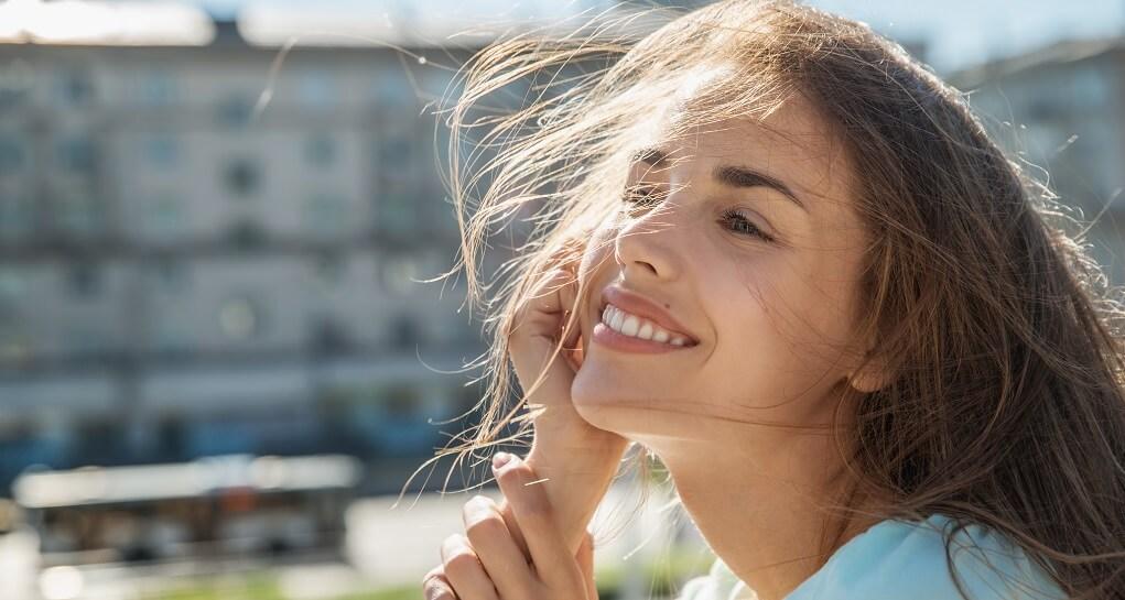 Donna sorridente al sole rischia photo aging